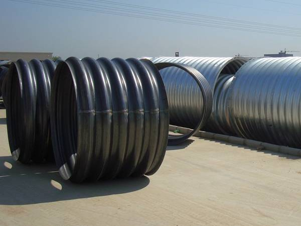Several integral corrugated steel pipes with black polymer coating and shiny zinc coating.